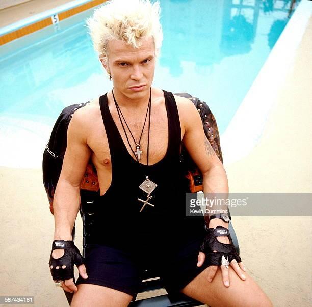 English rock singer Billy Idol sitting by a swimming pool, circa 1985.