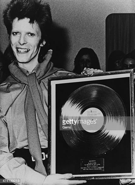 English rock singersongwriter David Bowie with a gold record awarded to him for 100 000 sales of his album 'The Rise and Fall of Ziggy Stardust and...