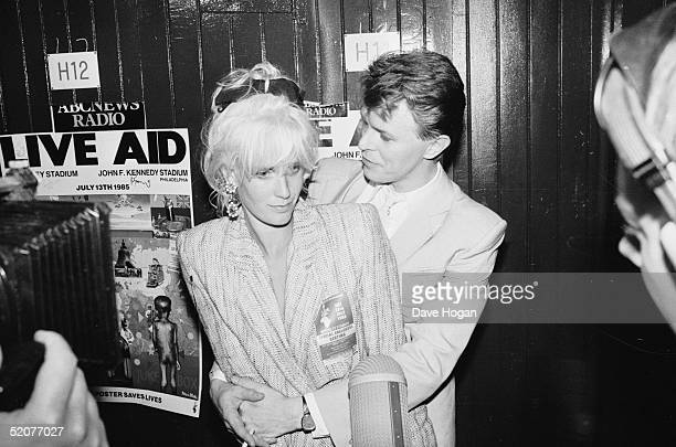 English rock star David Bowie backstage with TV presenter and wife of Bob Geldof Paula Yates at the Live Aid concert at Wembley Stadium London 13th...