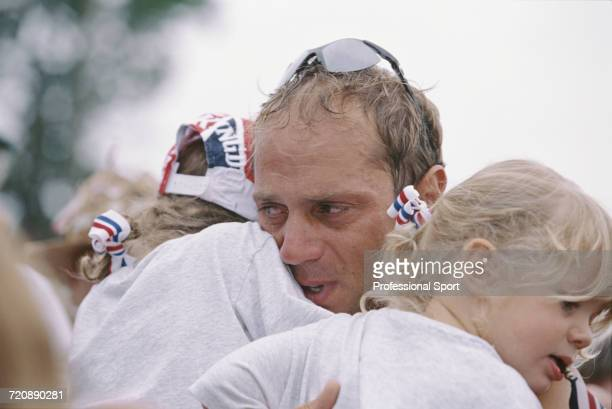 English rower Steve Redgrave holds his two daughters in his arms after finishing in first place with Matthew Pinsent to win the gold medal for Great...