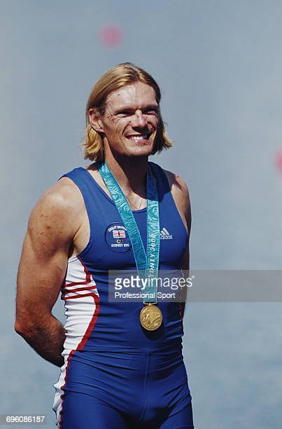 English rower Tim Foster pictured wearing his gold medal on the podium after the Great Britain team finished in first place to win the gold medal in...