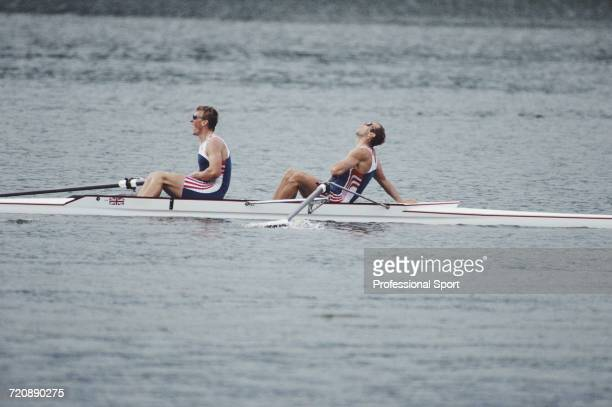 English rowers Matthew Pinsent and Steve Redgrave pictured sitting exhausted in their boat after finishing in first place for the Great Britain team...