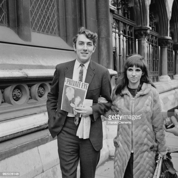 English satirist and comedian Peter Cook pictured holding a copy of the magazine Private Eye with his wife Wendy Snowden outside the Royal Courts of...