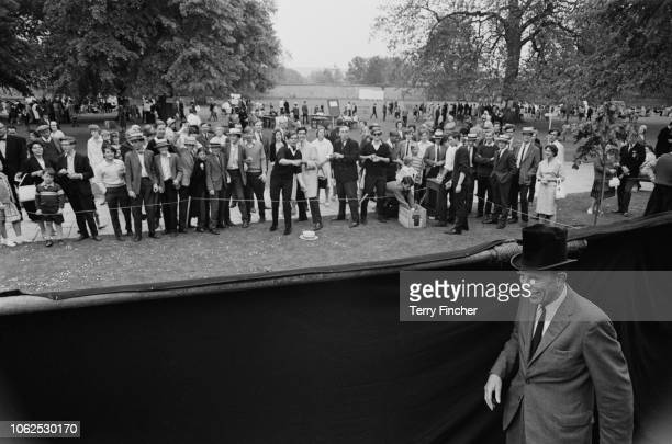 English scholar and Headmaster of Winchester College Desmond Lee pictured walking with a top hat behind a screen at an open day in the grounds of the...