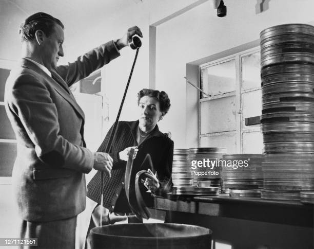 English screenwriter and director Muriel Box examines stacks of metal film reels with film producer William MacQuitty at her home in Mill Hill,...