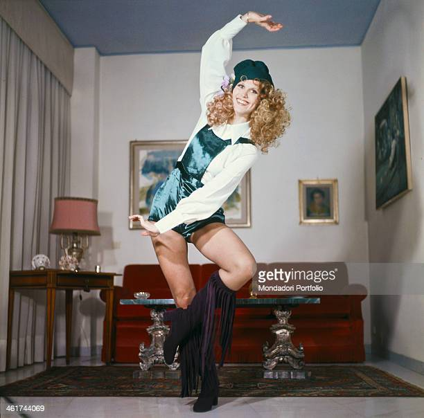 English Show girl and singer Minnie Minoprio born Virginia Anne Minoprio exteporizes a step of dance in the living room wearing boots with fringes...