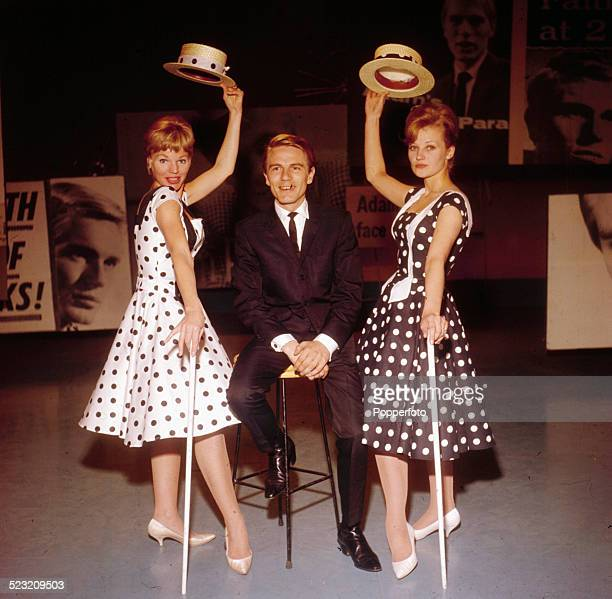 English singer Adam Faith posed in a television studio with two female dancers wearing polka dot dresses in 1963