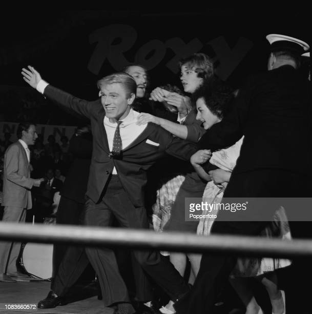 English singer Adam Faith is grabbed by teenage female fans during a performance at the Royal Albert Hall in London in October 1960
