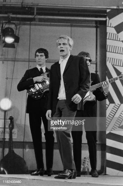 English singer Adam Faith performs live with bassist John Rogan and guitarist Russ Ballard of The Roulettes on the set of the music television show...