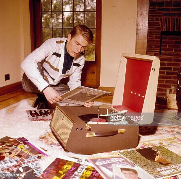 English singer Adam Faith pictured playing LP records on a record player at home in Surrey England in 1963
