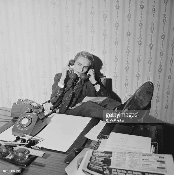 English singer Adam Faith pictured seated at an office desk answering two telephones simultaneously on 23rd December 1964 Adam Faith has just...