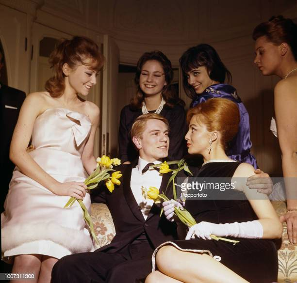English singer Adam Faith pictured seated on a sofa with a group of young French women and models at a theatre in August 1961