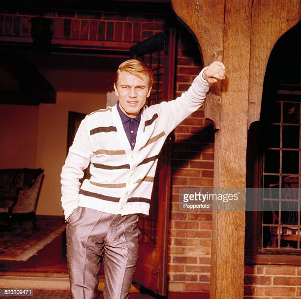 English singer Adam Faith pictured wearing a white striped cardigan stands outside his home in Surrey England in 1963
