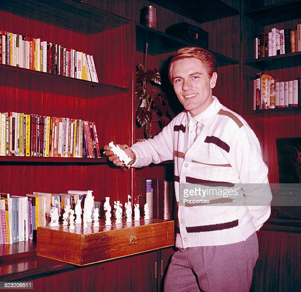 English singer Adam Faith pictured wearing a white striped cardigan whilst holding a piece from an ornate chess set in his library at home in Surrey...