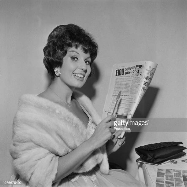 English singer Alma Cogan pictured entering a bingo crossword competition in a magazine in February 1962