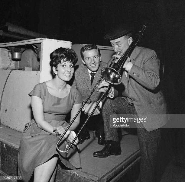 English singer Alma Cogan pictured with composer and singer Denis King and trombone player George Chisholm backstage during the Record Star Show at...