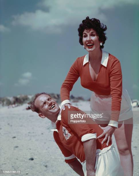 English singer Alma Cogan posed with English footballer and captain of Blackpool FC Harry Johnston on a beach near Blackpool England in August 1955...