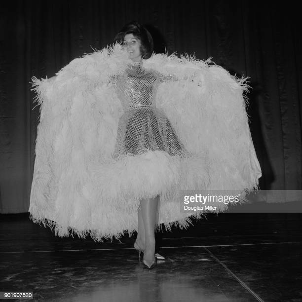 English singer Alma Cogan rehearses for a show at The Talk of the Town in London 6th January 1964 She is wearing a chainmail look dress and a cape of...