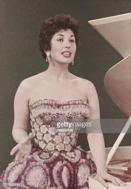 English singer Alma Cogan wearing a strapless gown performs on stage in England in 1955