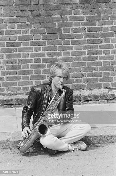 English singer and actor Adam Faith pictured in character as Frank from the television film 'Just Another Little Blues Song' playing a saxophone on a...