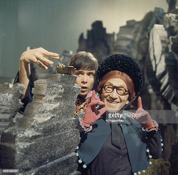 English singer and actor Cliff Richard pictured with the comedian Arthur Askey in a scene from the television adaptation of the pantomime 'Aladdin'...