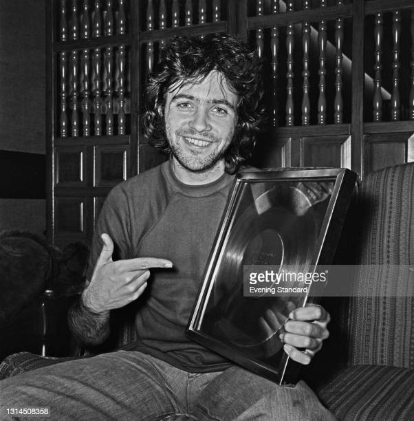 English singer and actor David Essex holding a gold disc awarded to him for 100,000 sales of his hit single 'Rock On', UK, 21st January 1974.