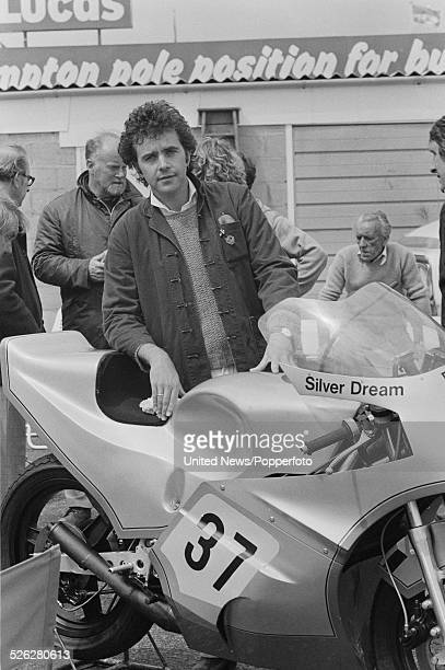 English singer and actor David Essex pictured with the Silver dream motorcycle at Silverstone motor racing circuit in England during production of...