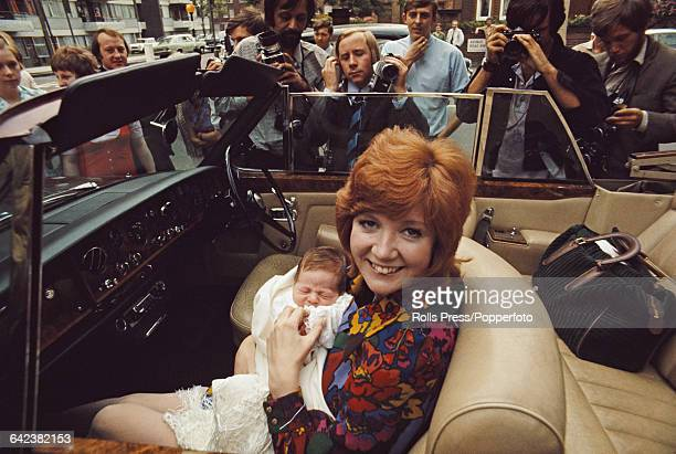 English singer and entertainer, Cilla Black pictured with her new born son Robert in the passenger seat of a open top car after being discharged from...