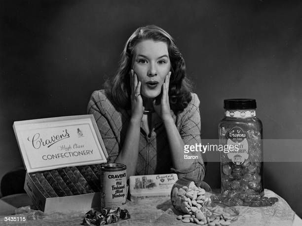 English singer and former child actress Sally Ann Howes gasps at the variety of sweets available during a break in rationing