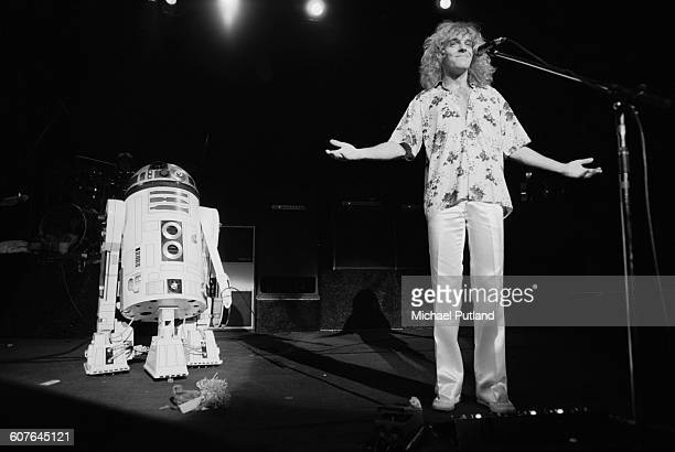 English singer and guitarist Peter Frampton appears bemused after the droid R2D2 from the film 'Star Wars' brought Frampton's guitar on stage for the...