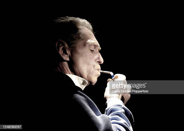 English singer and keyboard player Georgie Fame lights a cigarette on stage at Ronnie Scott's Jazz Club in Soho, London on 20th September 2004.