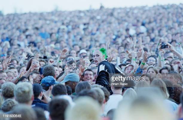 English singer and musician Keith Flint of The Prodigy crowd surfs amongst the audience during the group's support slot for rock group Oasis at...