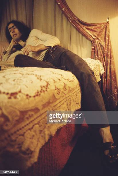 English singer and musician Paul Rodgers vocalist with rock group Free pictured lying on a bed smoking a cigarette on 24th August 1972