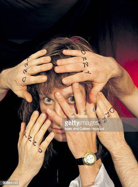 English singer and Ozzy Osbourne poses behind the fingers of the band members of the Blizzard of Ozz 1988