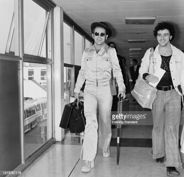 English singer and pianist Elton John arrives back in the UK at Heathrow Airport, at the end of his summer 1973 tour of the USA, 30th October 1973.