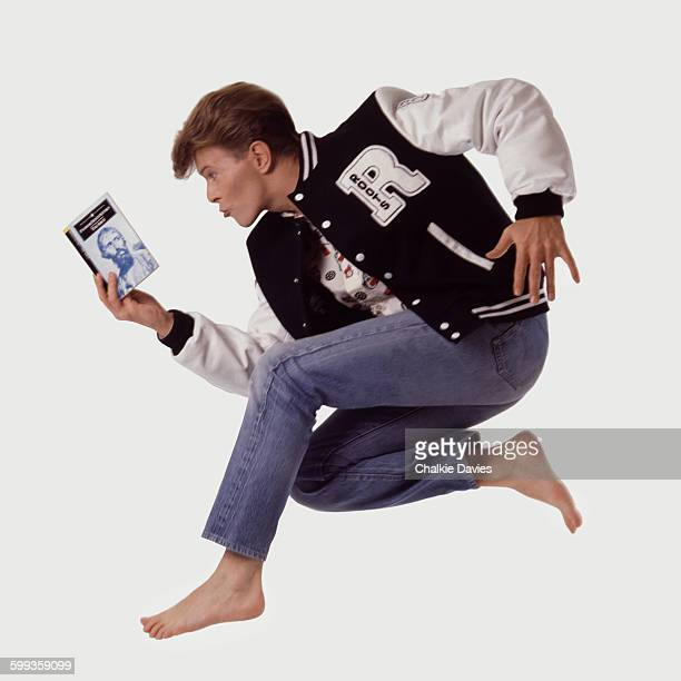 English singer and songwriter David Bowie wearing a letterman jacket and jumping in the air while reading 'The Idiot' by Fyodor Dostoyevsky London...