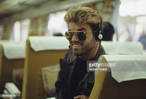 English singer and songwriter George Michael pictured listening to a walkman personal stereo device on a bullet train during the Japanese leg of his...