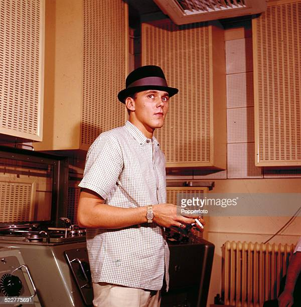 English singer Billy Fury posed wearing a checked shirt and trilby hat whilst smoking a cigarette in a recording studio in 1963