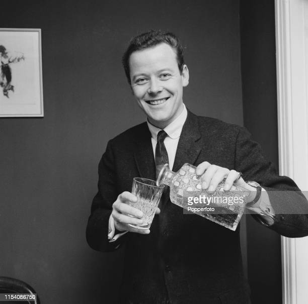 English singer Craig Douglas pours a drink from a cut glass decanter in May 1965