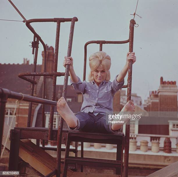 English singer Dusty Springfield pictured barefoot and wearing jeans and a blue shirt on a rooftop fire escape in London in 1963
