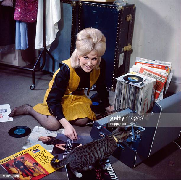 English singer Dusty Springfield pictured playing LP records including discs by The Shirelles and Peggy Lee with a cat in 1963