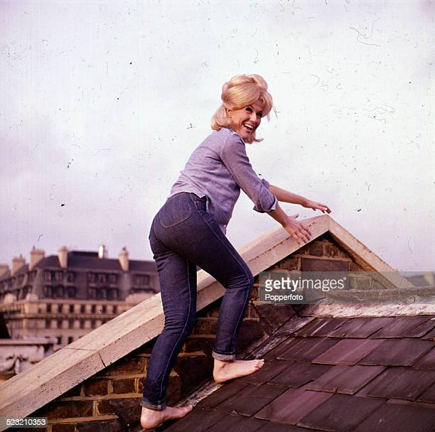 English singer Dusty Springfield pictured wearing jeans and a blue shirt whilst climbing barefoot on a slate roof in London in 1963