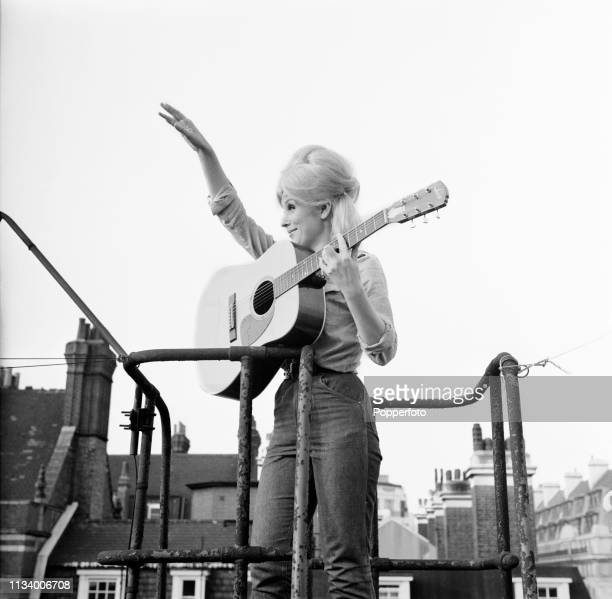 English singer Dusty Springfield pictured with an acoustic guitar on a rooftop fire escape in London in 1963