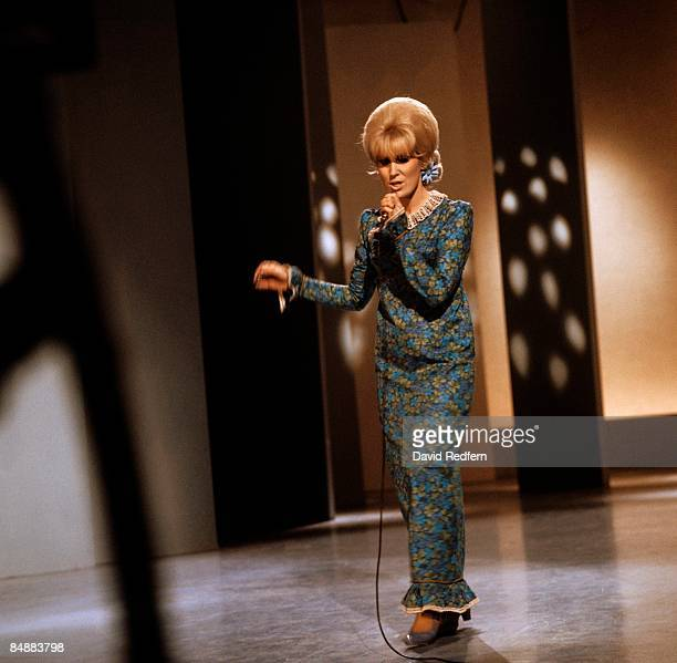 English singer Dusty Springfield , wearing a floral patterned dress, performs on the set of a television show circa 1967.