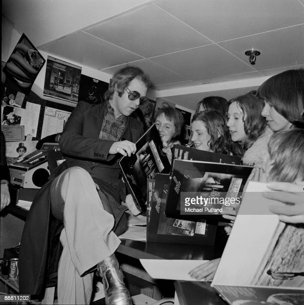 English singer Elton John signing copies of his new album 'Don't Shoot Me I'm Only the Piano Player' at Noel Edmond's Record Bar in the King's Road...