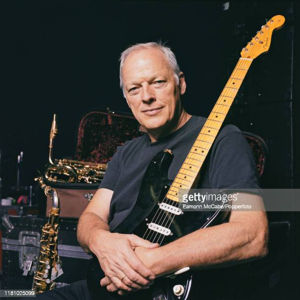English singer, guitarist and musician David Gilmour of Pink Floyd holds a black Fender Stratocaster guitar, nicknamed The Black Strat, during a...