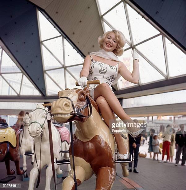 English singer Kathy Kirby posed sitting on a fairground carousel horse or merrygoround in 1964
