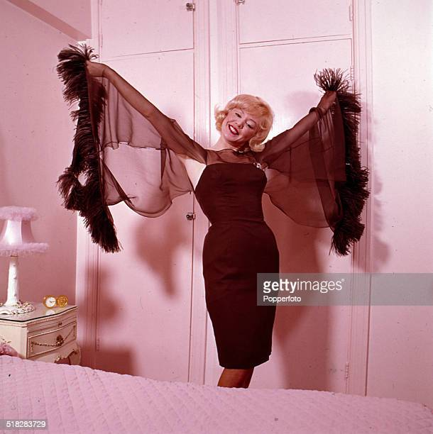 English singer Kathy Kirby posed wearing an evening dress with fine chiffon style sleeves in 1965