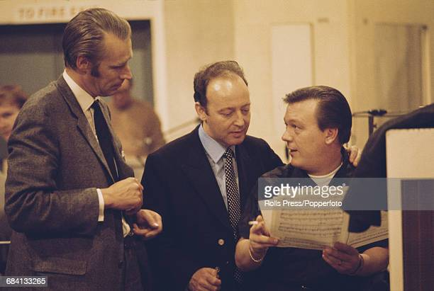 English singer Matt Monro pictured right in a recording studio with English record producer George Martin and an unidentified studio arranger during...