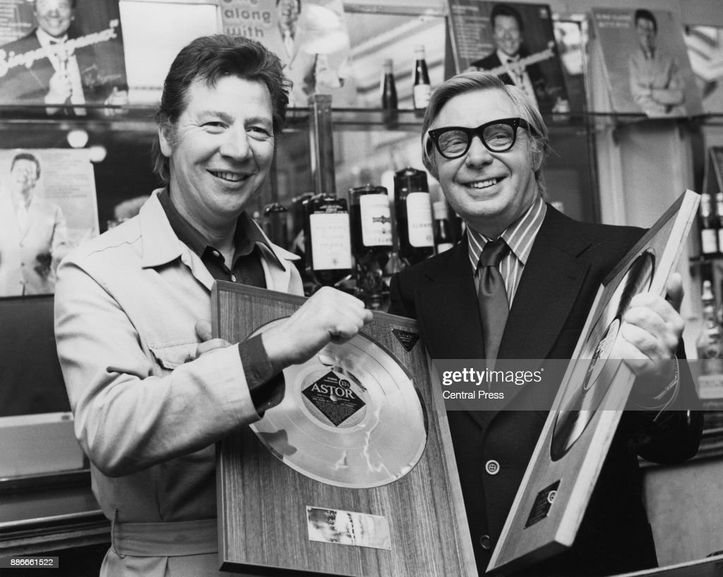 "English singer Max Bygraves (1922 - 2012, left) with musical director Cyril Stapleton (1914 - 1974, right) and two of the golden discs presented to him at ATV House in London, to mark the Australian success of his LPs 'Sing Along with Max' and ""The Golden Hour of Max Bygraves', 13th June 1973."